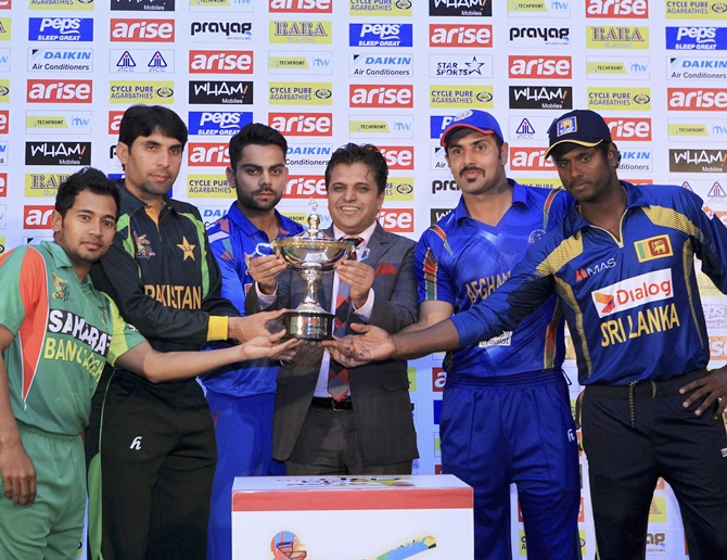 Cricket captains pose with the Asia Cup cricket tournament trophy during a ceremony in Dhaka
